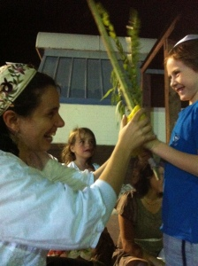Rabbi Na'ama Dafni-Kellen introduces a young child to the Lulav and Etrog.